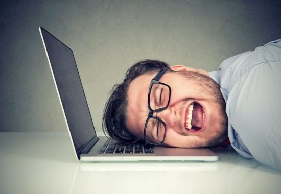 Frustrated-Looking Man Leaning On His Laptop Keyboard