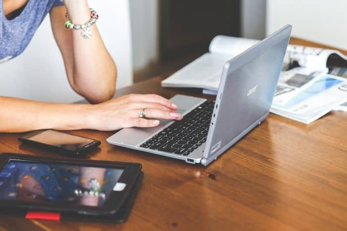 Woman Working At A Desk With A Laptop And A Tablet Beside Her