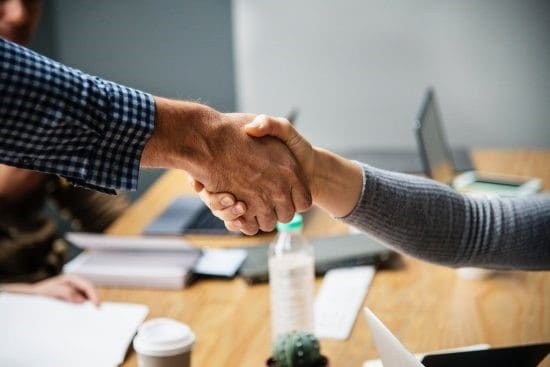 Two People Shaking Hands During A Business Meeting