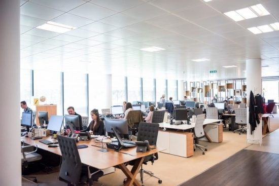 Workers Sat At Their Desks In An Open Plan Office